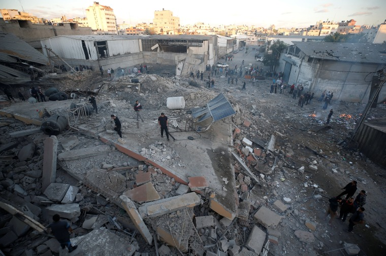 Image: Palestinians inspect the scene of an Israeli air strike on a building in Gaza City