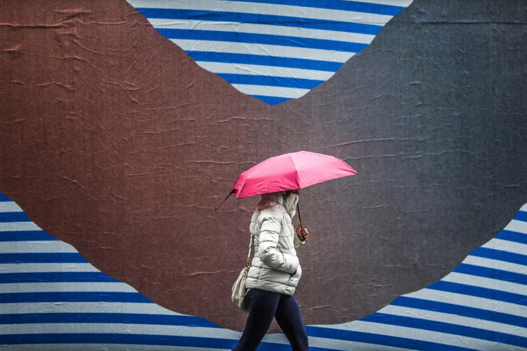 Image: A pedestrian walks under an umbrella during the rain in Manhattan