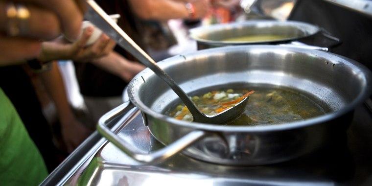 Man eats soup from public ladle