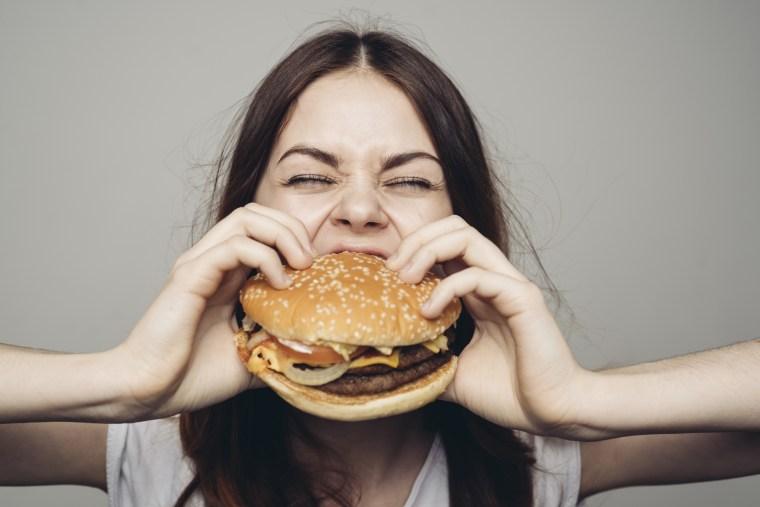 A woman eats a cheeseburger