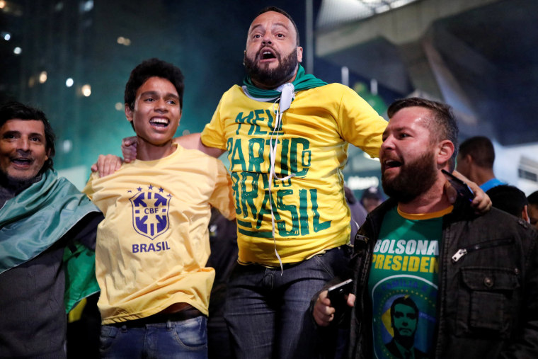 Image: Supporters of Jair Bolsonaro, far-right lawmaker and presidential candidate of the Social Liberal Party (PSL), react after polls closed in Sao Paulo