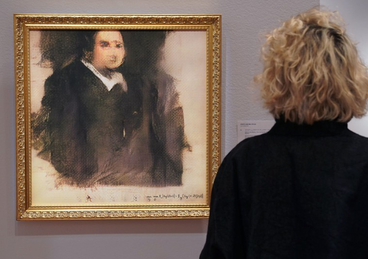 Image: A woman looks at a work of art created by an algorithm by French collective named OBVIOUS which produces art using artificial intelligence
