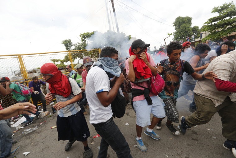 Image: Migrants break the fence between Guatemala and Mexico and fight police