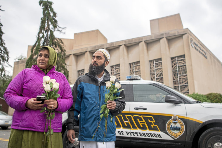 Samina Mohamedali, left, and her husband Kutub Ganiwalla, members of the Dawoodi Bohra Muslim community, both of North Hills, prepare to place flowers on a memorial in front of the Tree of Life Congregation in Squirrel Hill neighborhood of Pittsburgh on Oct. 28, 2018.