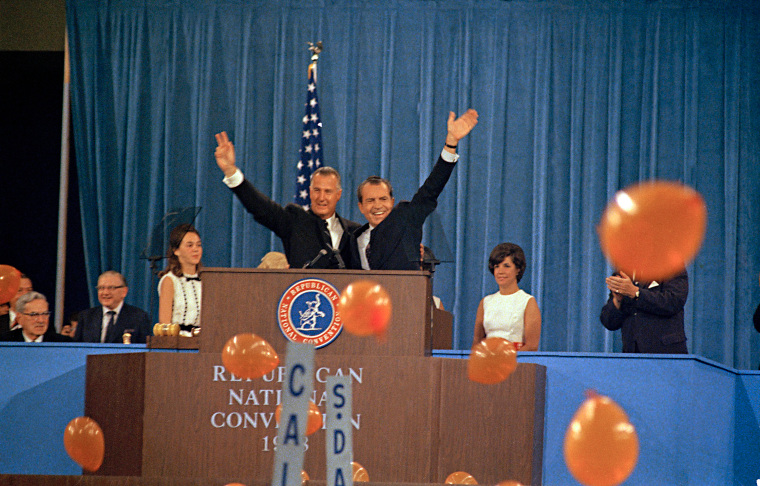 Republican presidential candidate Richard Nixon, waving right, and his running mate Spiro Agnew react to cheers