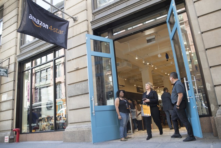 A shopper leaves the Amazon 4-star store in the Soho neighborhood of Manhattan after making a purchase