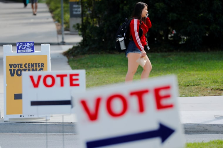 Image: Voting signs point to an early voting outdoor polling location on the University of Irvine campus in Irvine, California