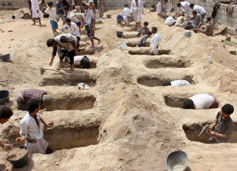 Image: Yemenis dig graves for children who were killed when their bus was hit during a Saudi-led coalition air strike