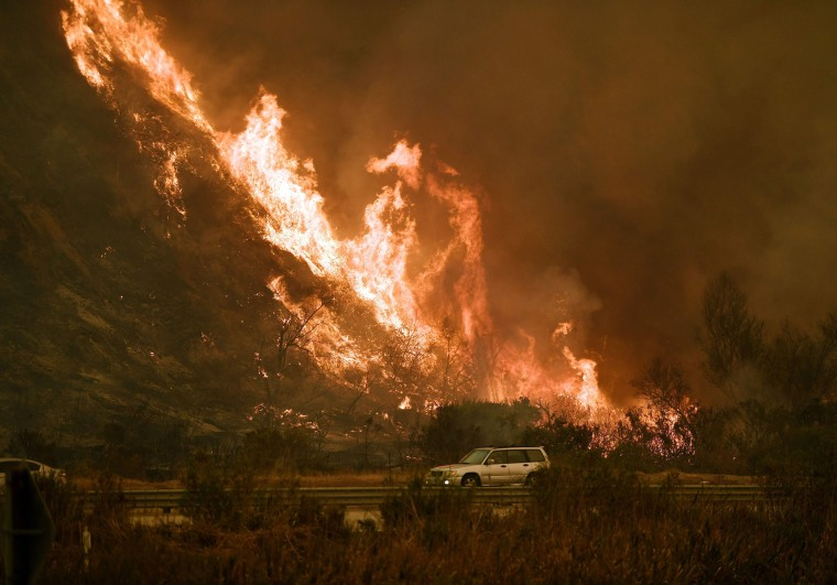 Image: Vehicles pass beside a wall of flames on the 101 highway as it reaches the coast during the Thomas wildfire near Ventura
