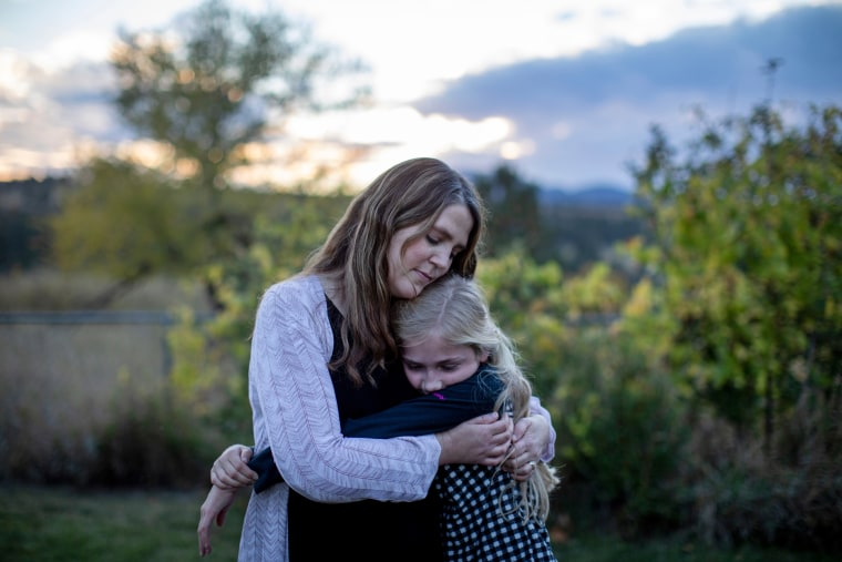 Kristen Kilmer hugs her 12-year-old daughter at their home in Spearfish, South Dakota.