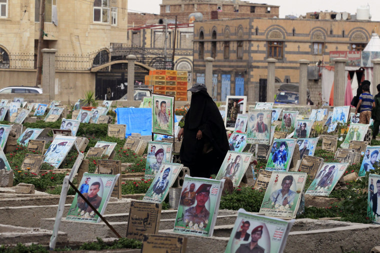 Image: A woman walks among graves with portraits of Houthi militia members
