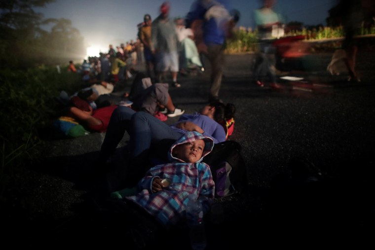 Image: Glenda Escobar, part of a caravan of thousands from Central America en route to the United States, rests on the road with her son Adonai, as they make their way to Pijijiapan from Mapastepec