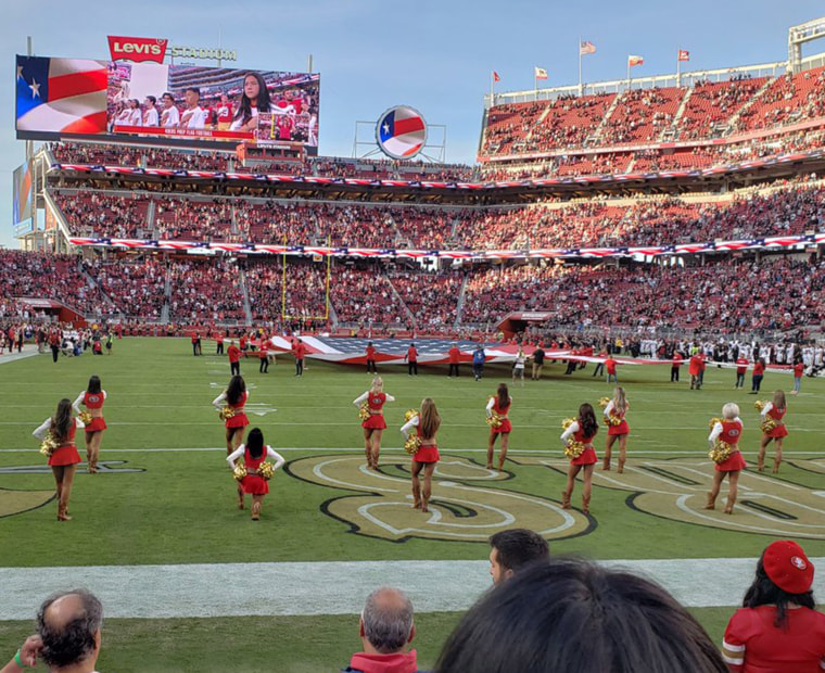 Image: A San Francisco 49ers cheerleader kneels during the national anthem