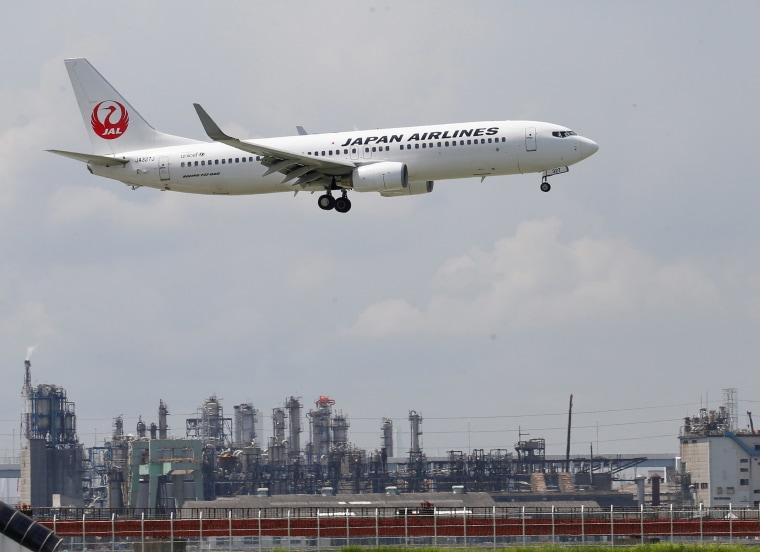 Image: Japan Airlines' airplane flies near Haneda Airport in Tokyo