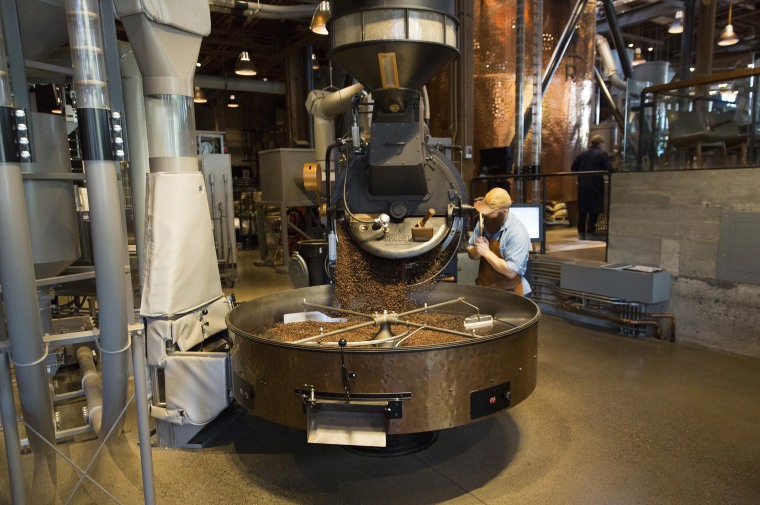 Image: A coffee roaster empties freshly roasted coffee beans from the small-batch roaster at the Starbucks Reserve Roastery and Tasting Room in Seattle