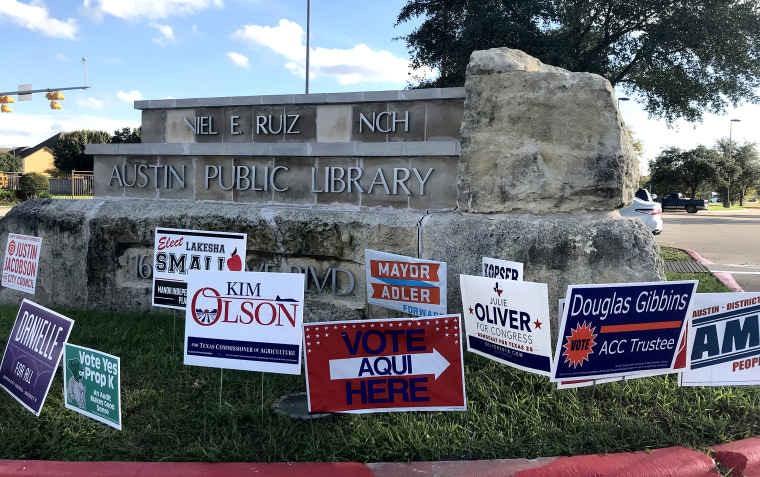 Early voting location sign sits among candidates' signs at the entrance to the Daniel E. Ruiz branch of the Austin Public Library in East Austin, Texas