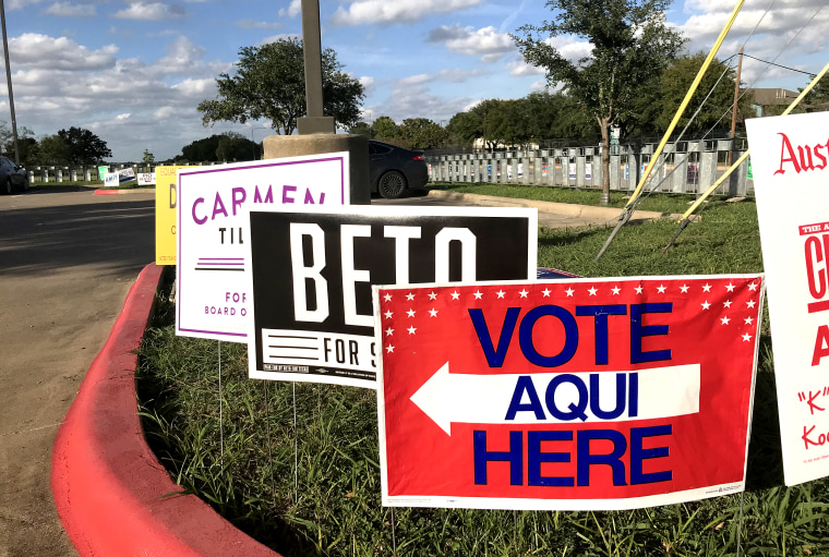A Spanish-language sign directs voters to an early voting polling location in east Austin, in front of a campaign sign for Beto O'Rourke, a Democratic candidate for U.S. Senate.
