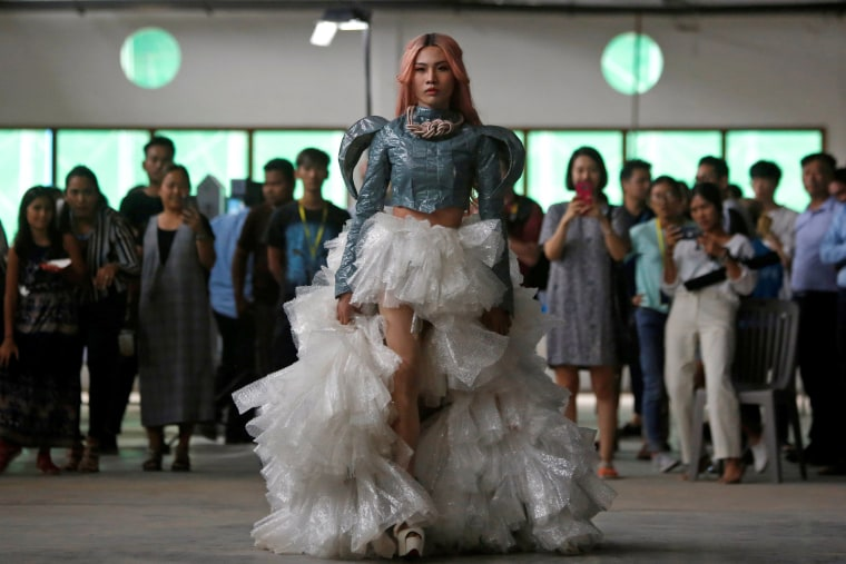 Image: A model wears a dress made out of recycled material during a show organised by LGBT fashion designers to battles discrimination in Phnom Penh