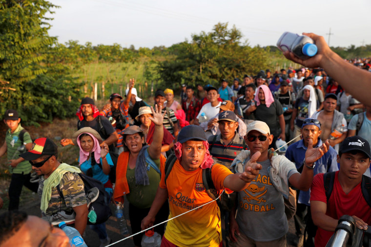 Image: Migrants, part of a caravan traveling from Central America en route to the United States walk by the road that links Ciudad Hidalgo with Tapachula