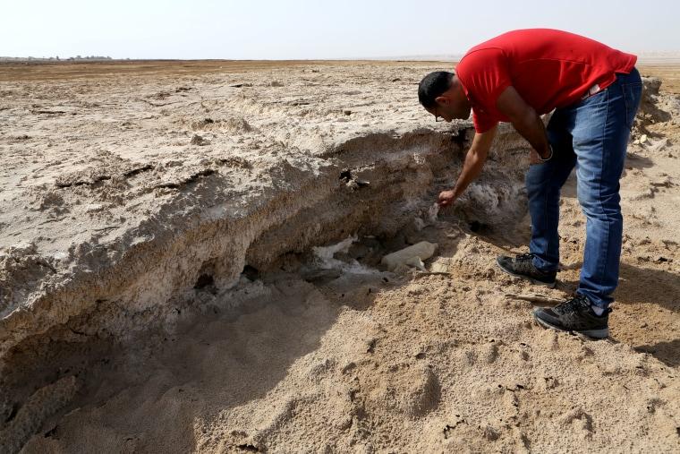 Image: EcoPeace engineer Eshak Alguza breaks off a chunk of salt on what used to be bottom of the Dead Sea