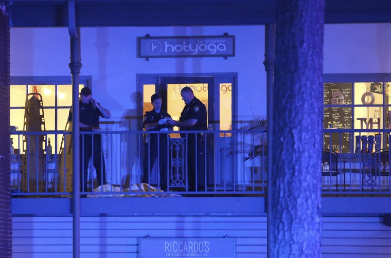 Police investigate the scene of a shooting at a yoga studio in Tallahassee, Florida