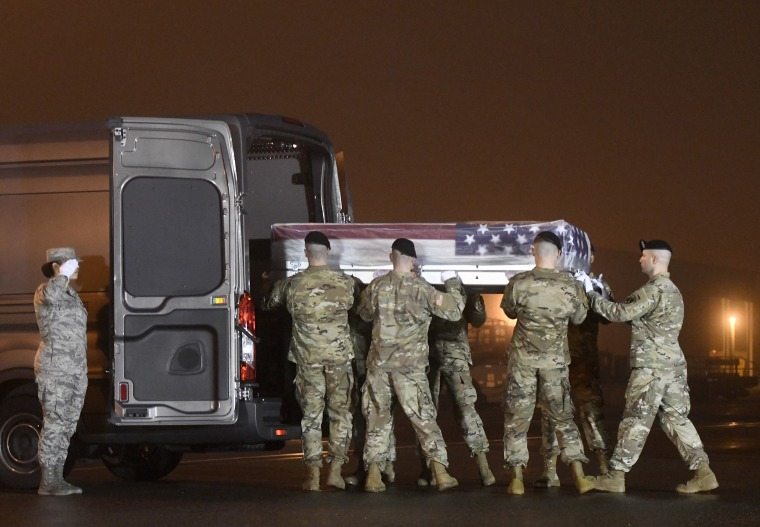 Image: An Army carry team loads into a vehicle a transfer case containing the remains of Maj. Brent R. Taylor at Dover Air Force Base