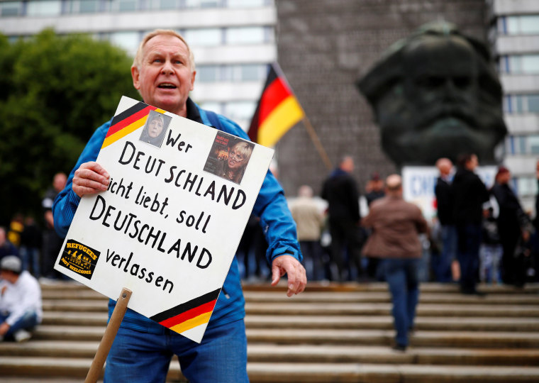 "Image: A far right demonstrator in Chemnitz, Germany holds a placard reading ""Whoever does not love Germany should leave Germany"""