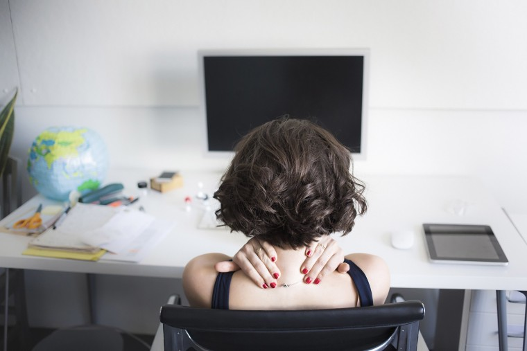 Image: Young woman massaging her neck at desk