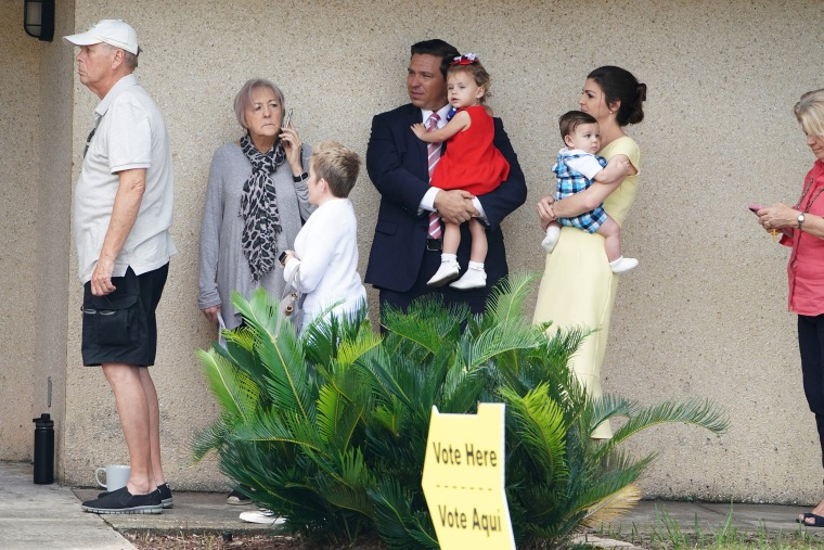 Image: Republican candidate for Governor Ron DeSantis, carrying his daughter Madison, and his wife Casey DeSantis with their son Mason stand in line to vote in the midterm election at a polling place in Ponte Vedra Beach