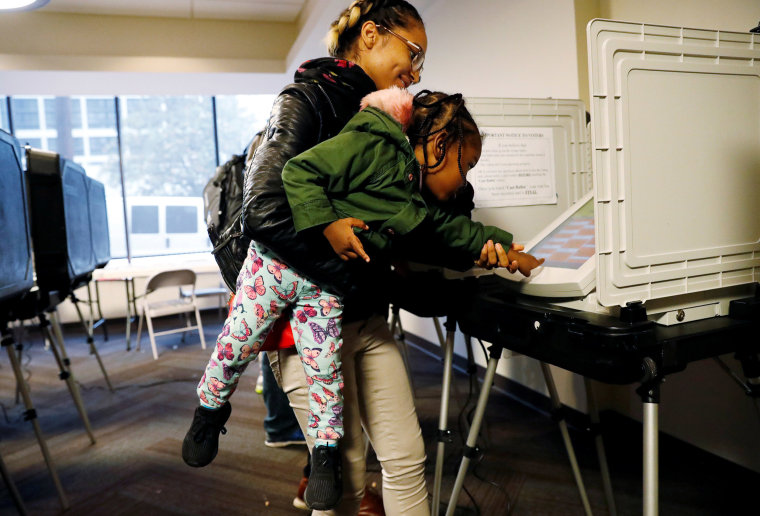 Image: Lindsey Adams lets her daughter Kadence Bethea help her vote in U.S. midterm election in Atlanta