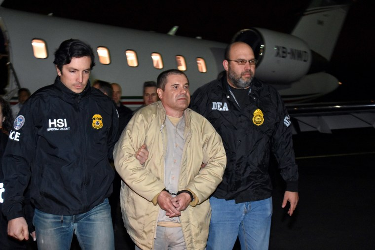 "Image: Authorities escort Joaquin ""El Chapo"" Guzman, center, from a plane to a waiting caravan of SUVs at Long Island MacArthur Airport"