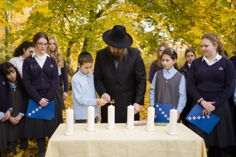 Rabbi Yehuda Teichtal lights candles with students during an event to mark the 80th anniversary of Kristallnacht in Berlin