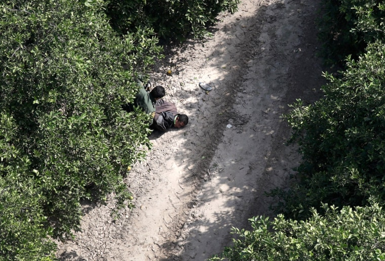 A U.S. Border Patrol agent detains an undocumented immigrant on Nov. 6, 2018 in McAllen, Texas. Border Patrol agents on the ground, assisted by a helicopter unit of U.S. Air and Marine Operations agents, apprehended a group of immigrants who had crossed the border illegally from Mexico.