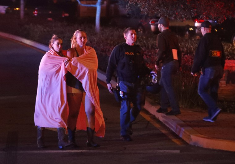Image: Two women wearing blankets leave the area near the Borderline Bar and Grill in Thousand Oaks, California