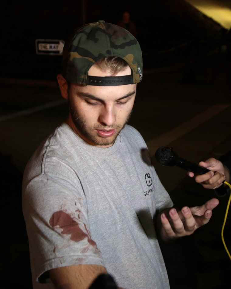 Matt Wennerstorm, who has blood on his shirt, talks to the media outside the scene of the shooting.