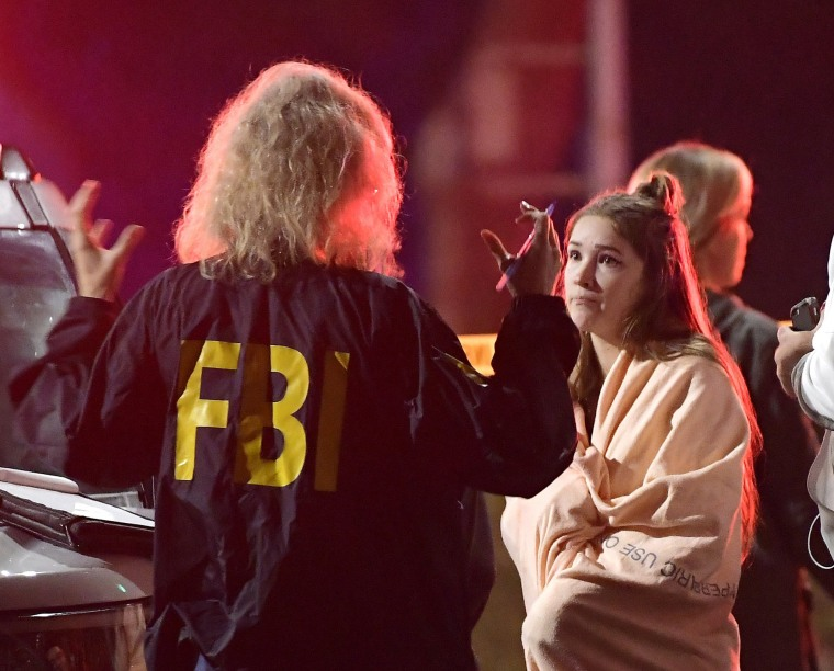 An FBI agent speaks to a potential witness outside of the Borderline Bar and Grill.