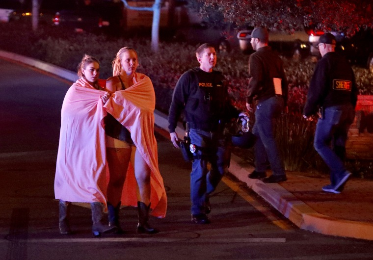 Two women leave the scene of the shooting in Thousand Oaks