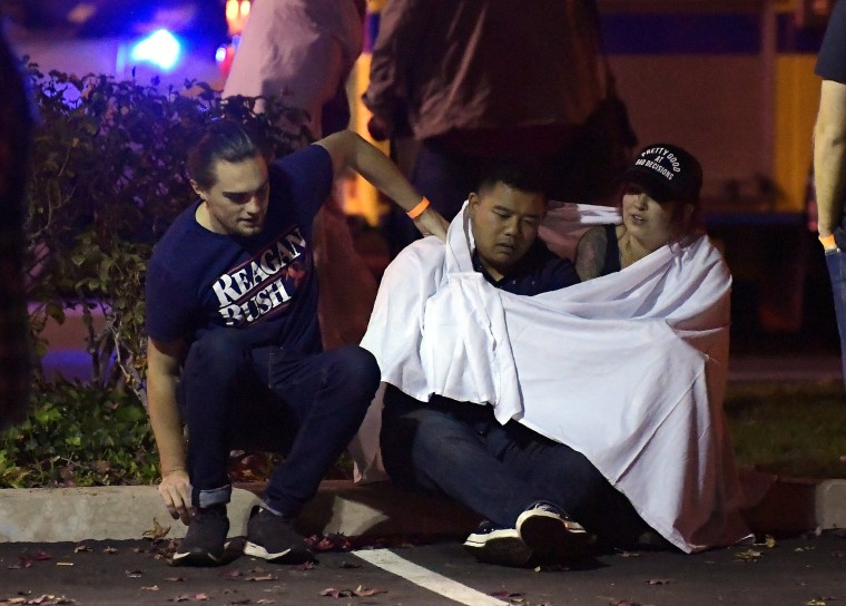 People comfort one another after a gunman killed twelve people at the Borderline Bar and Grill