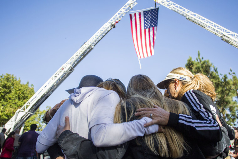 Mourners comfort one another during the procession of Sgt. Ron Helus, who was killed in the shooting at the Borderline Bar and Grill, in Thousand Oaks, California, on Nov. 8, 2018.