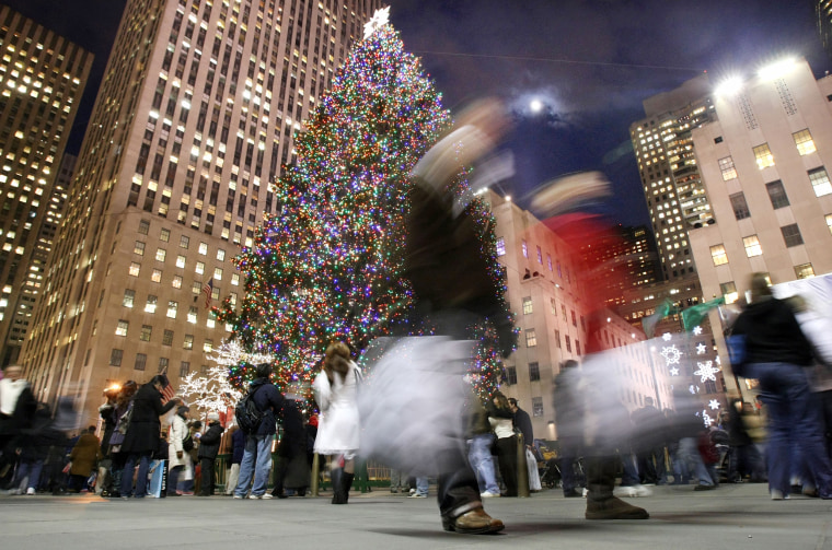 Shoppers walk past the Rockefeller Center Christmas tree in New York.