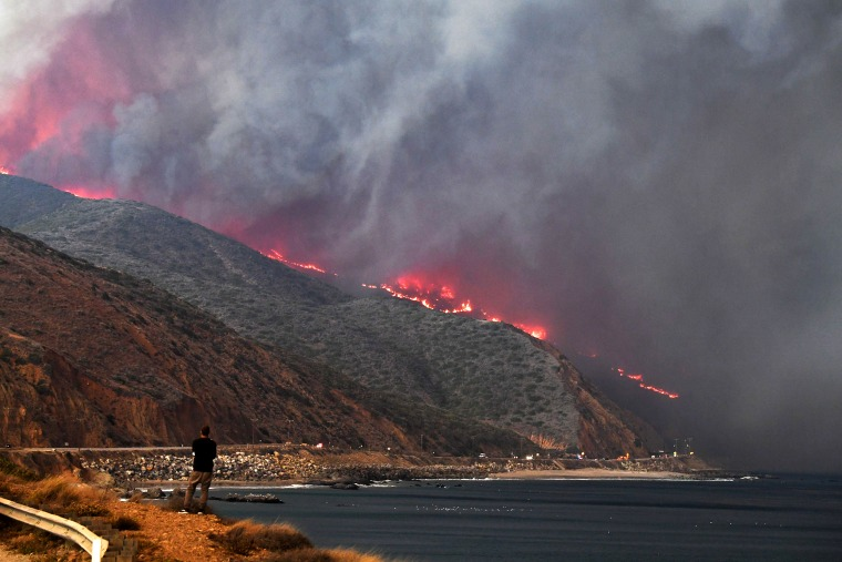 Image: A man watches as the Woolsey Fire reaches the ocean along Pacific Coast Highway (Highway 1) near Malibu, California, Nov. 9, 2018