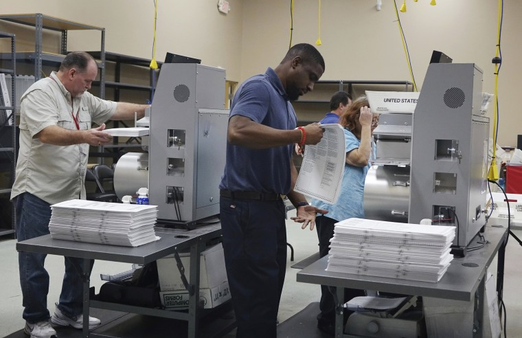 Election workers place ballots into electronic counting machines, on Nov. 11, 2018, at the Broward Supervisor of Elections office in Lauderhill, Florida. The Florida recount began Sunday morning in Broward County.