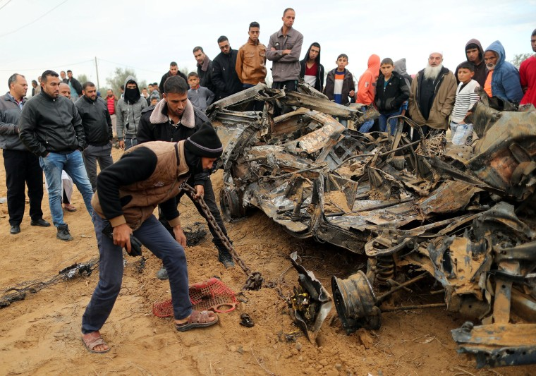 Image: Palestinians inspect the remains of a vehicle that was destroyed in an Israeli air strike, in Khan Younis in the southern Gaza Strip