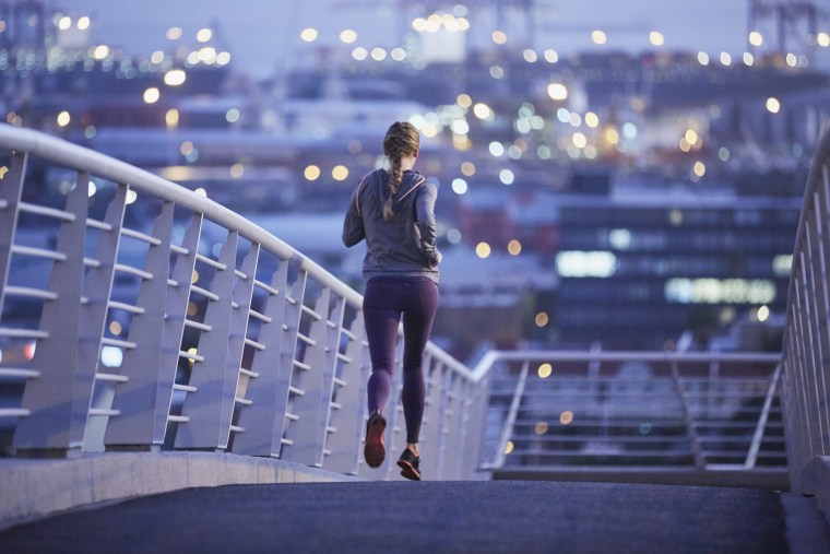 Female runner running on urban footbridge at dawn