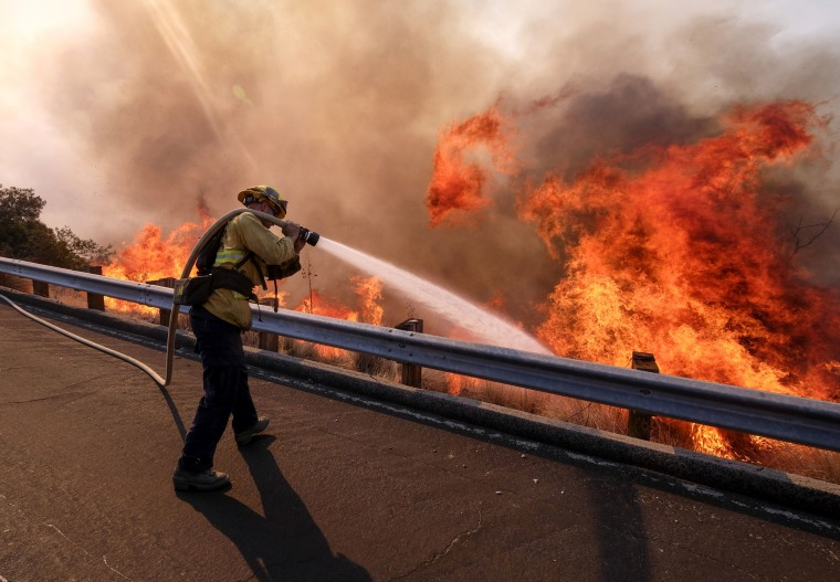 A firefighter battles a fire along the Ronald Reagan Freeway in Simi Valley, California on Nov. 12, 2018.