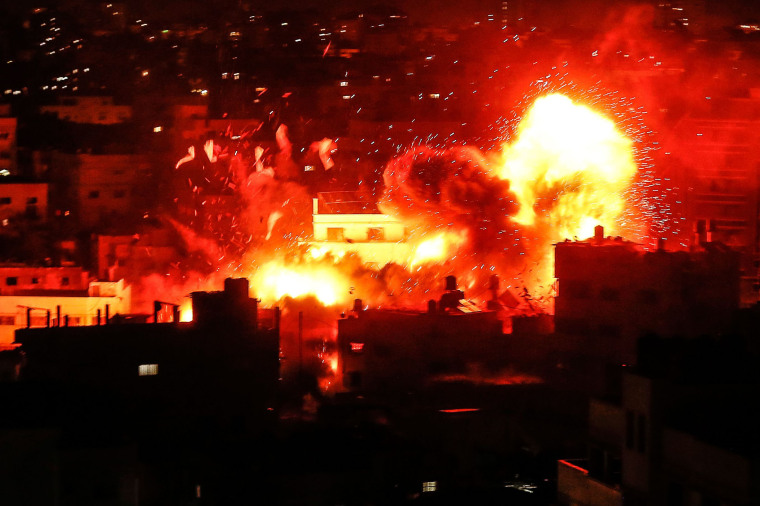 Image: A ball of fire above the building housing the Hamas-run television station al-Aqsa TV in the Gaza Strip