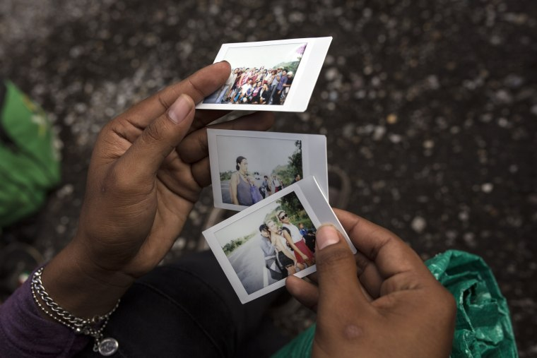 A member of the group looks at polaroid photos documenting their journey on the road to Sayula, Mexico, on Nov. 3, 2018.
