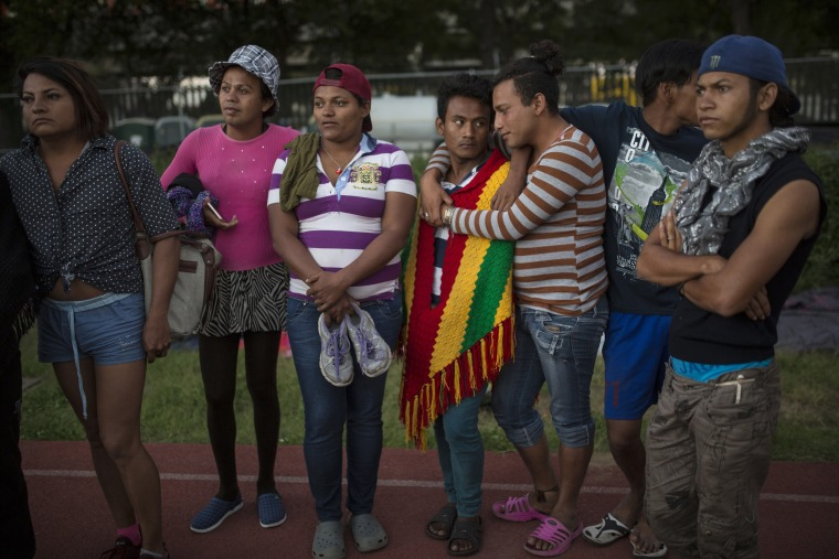 Migrants stand on the race track at the Jesus Martinez stadium, which was turned into a makeshift shelter for the migrant caravan, in Mexico City.
