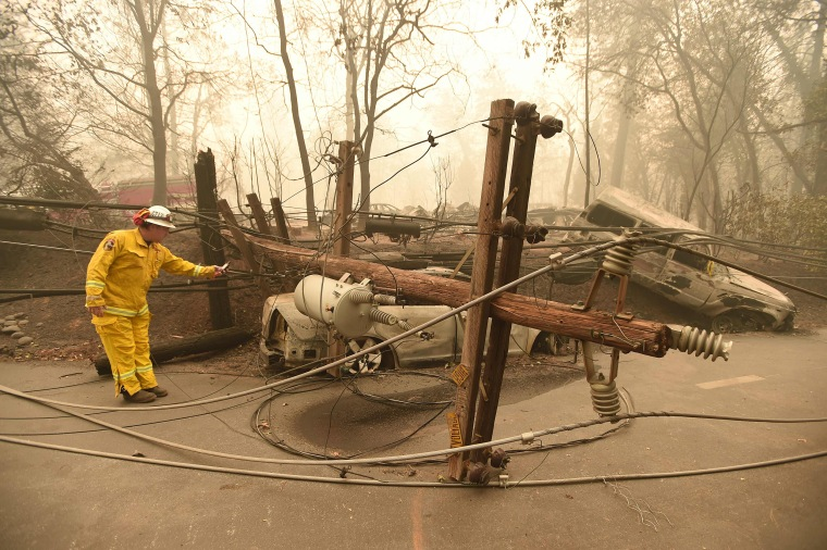 Image: CalFire firefighter Scott Wit surveys burnt out vehicles near a fallen power line on the side of the road after the Camp fire tore through the area in Paradise, California on Nov. 10, 2018.