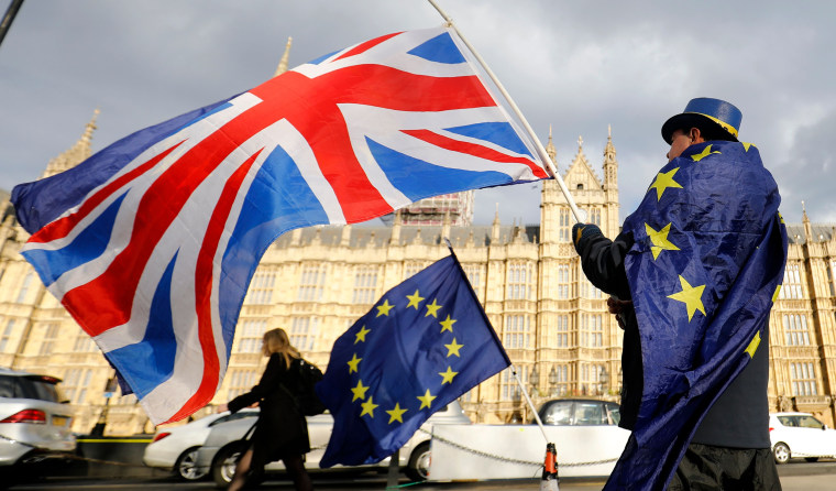 Image: An anti-Brexit demonstrator waves a Union flag alongside a European Union flag outside the Houses of Parliament in London, on March 28, 2018.